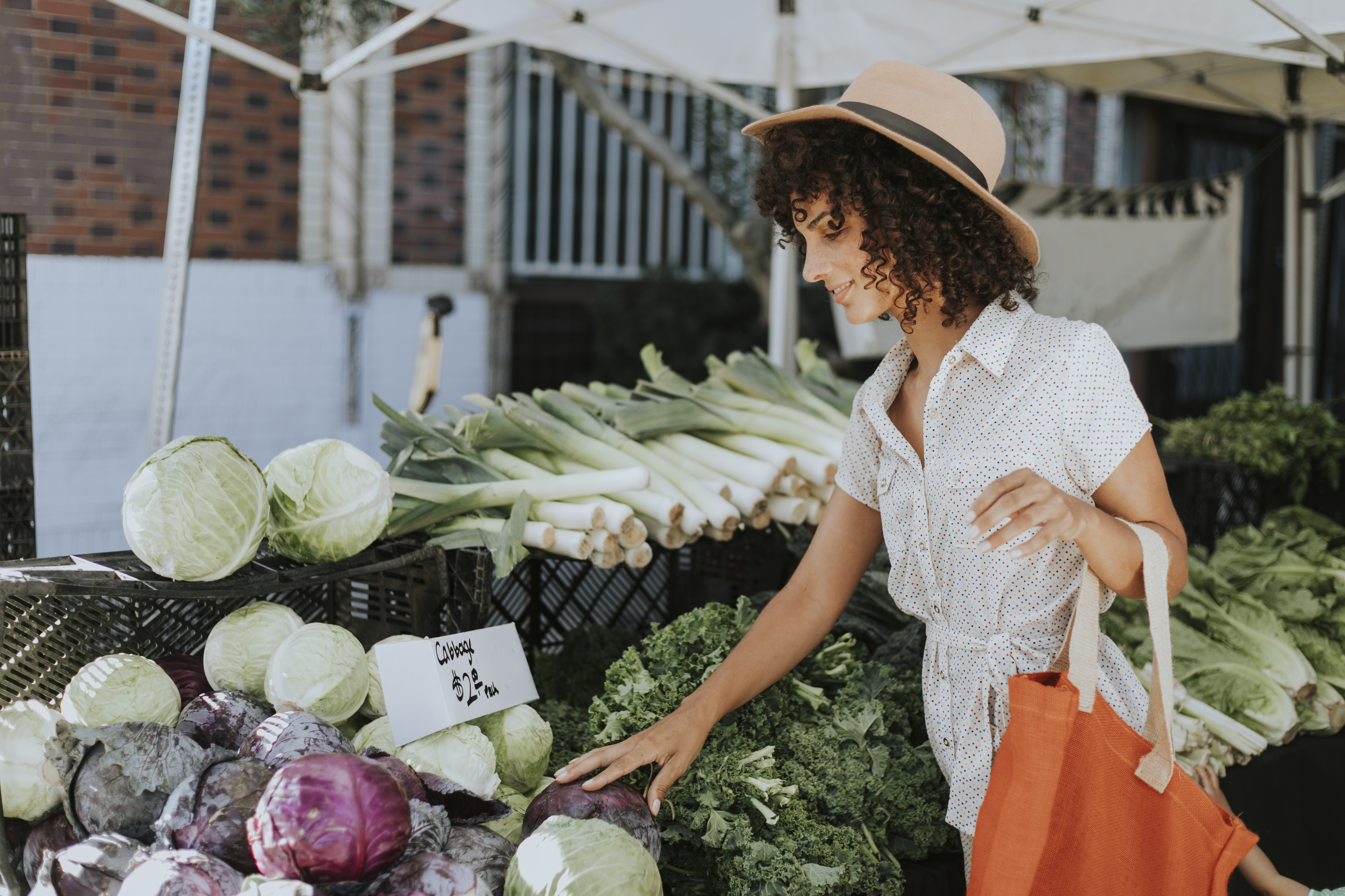 Healthy woman buying vegetables at a farmers market