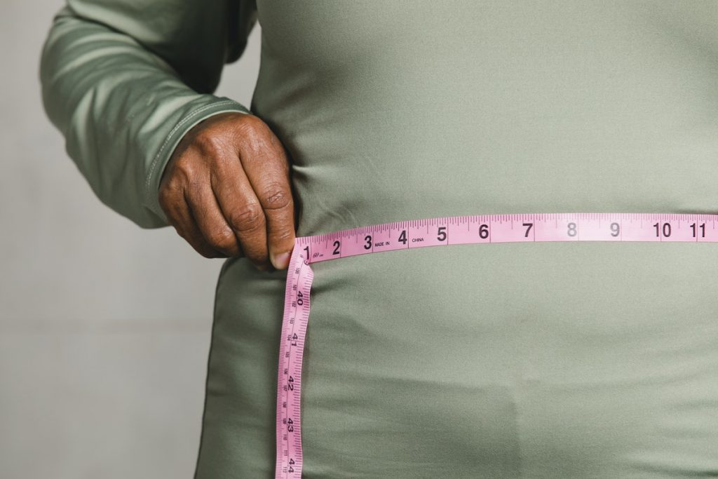 A person measuring their own waist circumference as part of a biometric screening