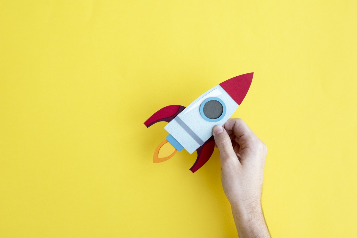 A cutout of a rocket ship in front of a yellow background